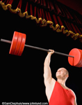 Picture of a body builder holding a barbell up over his head with just one arm.   The weights are orange as is his tank top. The man with the barbells is in a theater for a competition.